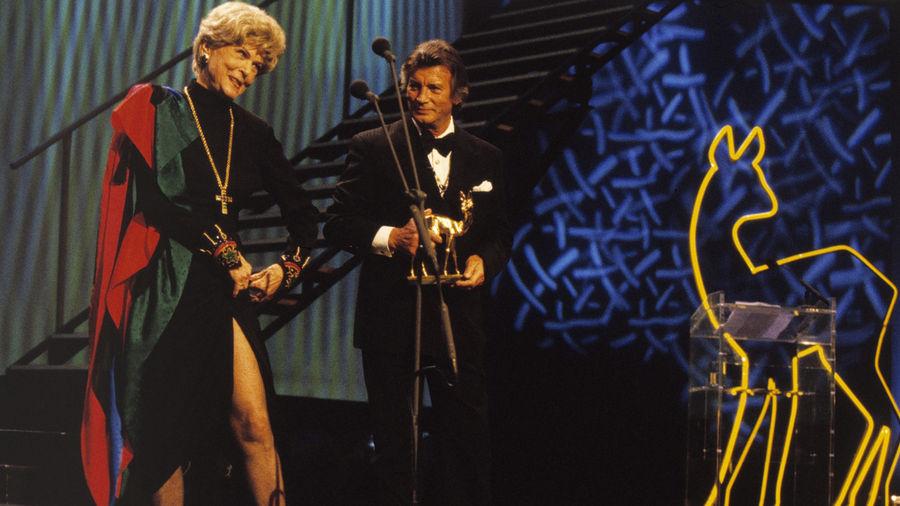 """Oha! Und das mit 85 Jahren! Marika Rökk zeigte """"Winnetou"""" Pierre Brice und dem Karlsruher Publikum ihre Beine. Rökk, 50 Jahre zuvor erste BAMBI-Preisträgerin, wurde mit dem Jubiläums-Bambi ausgezeichnet."""